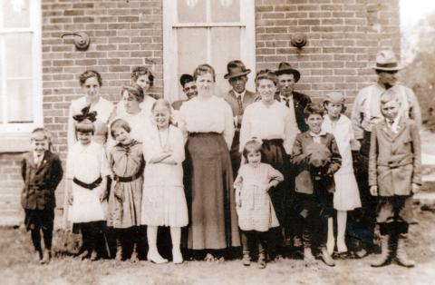 Pleasant Grove congregation standing in front of the adjacent school, 1917  Galen and his dad, Tom Sowers, Bertha Hass Clara Sowers, George R. and Martha Sowers, Balus and Lena Howard, George W. Sowers Jr., Myrtle Sowers, Pearl Sowers, Viola Hass, Mrs. Hass, Burnice and Bernita Howland, Jeanette and Dorothy Sowers